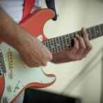 beide handen op de gitaar